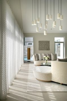 modern vs. contemporary This contemporary all-white living room showcases a custom cascading light fixture and sweeping glass windows with sheer textured curtains.