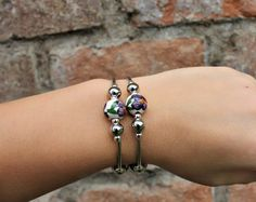This wrap bracelet is made out of hand painted ceramic beads and silver colored spacers and beads. Beaded Wrap Bracelets, Ceramic Beads, Hand Painted Ceramics, Floral, Silver, Etsy, Color, Jewelry, Hand Painted Pottery