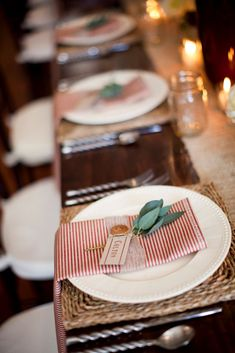 Stripey napkins, burlap napkin rings and placecards finished off with green stems, all upon a woven placemat - love
