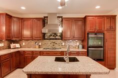 """This stunning #GraniteTransformations #kitchen was created with: Terra Di Siena #countertops with Metropolis Bronzite beveled edge #backsplash, with Metropolis Buxy behind the fan. The #floor is Terra Chiara #granite 16""""x16"""". The #cabinets doors are Revere in Cherry Select wood with Cayenne stain and iron glaze."""