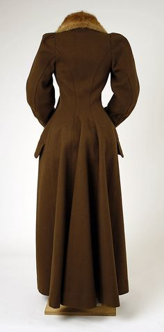 Nineties Costume for Women. Brown wool overcoat with fur trim, British, ca. 1891. Coats ranged from fitted to full, from short to floor length. Collars stood high and sleeves were large.