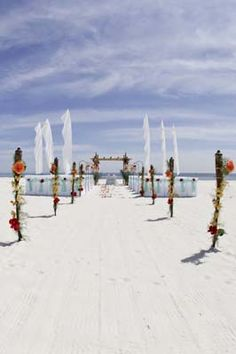 Sand Dollar beach wedding package with tiki torches, shepherds hooks with flowers, white chair covers with mint sashes and red flowers. Bamboo arbor with flowers and drapery. Beautiful Orange Beach and Gulf Shores Alabama Beach wedding packages. All-Inclusive, Custom, Create your own.