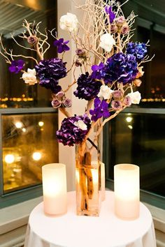 Incredible Purple Wedding Centerpiece- assorted purple flowers with lean branches in tall glass vases