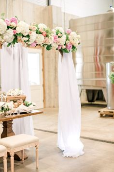 Wedding floral arrangement in the style of a chuppah with pink, blush, and white flowers and draping white curtains - perfect for Jewish wedding ceremony for a spring or summer wedding #weddingflowersspring #weddingflowerssummer #chuppah