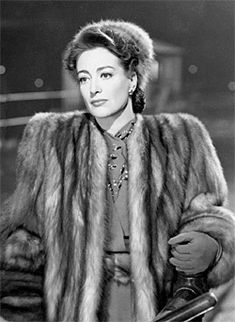 """Our first sight of JOAN CRAWFORD in """"Mildred Pierce"""" (1945) is the Crawford many of us have in mind: Wearing an impossibly broad-shouldered mink swing coat with matching hat, long dark hair, thick black eyebrows and a huge, lipsticked mouth to match her huge, haunted eyes."""