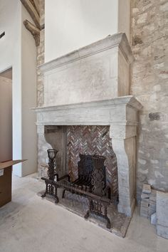 """This is the 190 year old French fireplace purchased in France.  The Ironwork is done by Theodore Docteur... a very gifted architectural blacksmiith making all of these stunning pieces with a large anvil.  He has done work for clients all over the world. Notice the thickness of scale on the fireplace grate.  3"""" thick."""