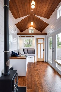 The spacious interior includes a Hobbit wood stove, corner nook with storage below, and a pull-out larder pantry in the storage staircase.