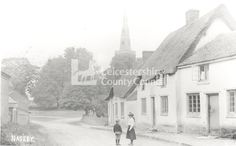 Naseby lies 7 miles to the south west of Market Harborough. It is the village from which the decisive battle of Naesby in the English Civil war got its name. Here two children stand in the road in 1907 without any fear of oncoming traffic.   In the background can be seen the spire of the parish church which was not completed until the 1860s. Just out of view behind the thatched cottage was the village forge. This image is a copy photograph of the original postcard.