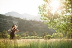 An Air Academy High School senior girl plays the violin during her high school senior pictures at Ute Valley Park in Colorado Springs with m...