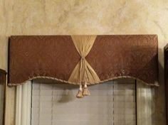Cornice board covered with material, now adding (Using glue gun)rope type trim…