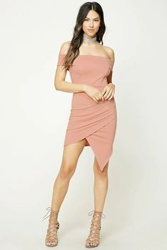 A stretch-knit dress featuring an off-the-shoulder neckline, short sleeves, ruching on one side, and an asymmetrical hem.