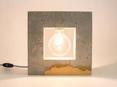 A table lamp made of concrete and wood. Inscrito, translated from Spanish, means Inscribed. It relates to the basic shape that served as the starting point for this design, a circle inscribed in a square. This represents the unfortunately very common situation in which forward thinking and liberal views (represented here by the round bulb) are blocked by compolsive conservative ideals (represented by the square block of concrete). The design is inspired by the ability of those represented by…