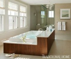 This freestanding soaking tub encased in beautiful walnut is a stunning focal point in the bathroom. - Traditional Home ® / Photo: Eric Roth / Design: Daniel Reynolds