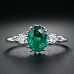 Estate Emerald and Diamond Ring.  A richly saturated, bright and lively, deep-green, faceted oval emerald, weighing 1.25 carats, glows from between a pair of sparkling white round brilliant-cut diamonds. The three gemstones are nestled in multi-prong basket-style settings handcrafted in gleaming 18 karat white gold. A colorful and enchanting jewel suitable as a non-conformist engagement ring.