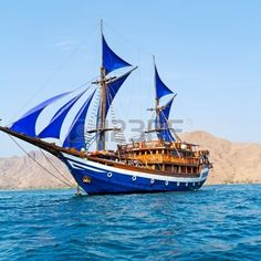 Vintage Wooden Ship with Blue Sails near Komodo Island, Indonesia Stock Photo