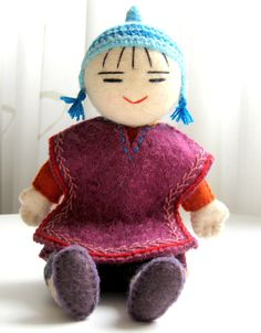 This decorative felt figure depicts a nomadic Kyrgyz girl, wearing a Kyrgyz coat of felted wool, finished with beautiful embroidered detail. She wears