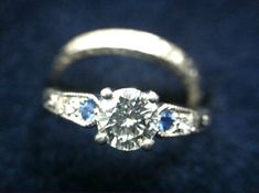 Beautiful and unique 5-year-old engagement ring and 3-year-old wedding band. Both engraved with 1920's style art deco filigree. Excellent condition.    Engagement ring has a center round-cut brilliant 0.70 carat diamond, VS-1 clarity, G color, moderate blue florescence, comes with GIA certificate. Two small side sapphires and two small side diamonds.