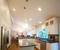 The existing kitchen had a dropped ceiling.  We removed the dropped ceiling and vaulted the kitchen.  The kitchen and dining room are opened to each other with spacious vaulted ceilings.  The cabinets are white painted shaker style cabinets with Caesarstone quartz countertops. H2D Architecture + Design