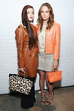 Odeya Rush and Brie Larson at the Coach F/W 15 presentation. On Odeya: Coach trench coat from the Pre-Fall 15 collection, Cotton Flare Trousers, and Swagger Carryall in Wild Beast Print. On Brie: Coach jacket, dress, and Swagger 20 Carryall Bag in Tangerine with ankle strap heeled sandals