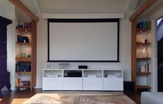 How to hide the TV - projector with screen! The screen can be rolled up and hidden in the custom made box (white box on top). The screen has a 5 cm distance from the wall making it possible to hang art on the back of the screen.