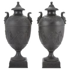 Pair of Wedgwood Basalt Urns  Each with loop handles molded with satyr masks, above a band of classical figures, on a leafy socle ending in a square base.