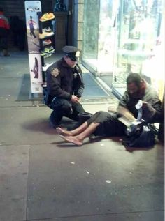 NY Cop giving a brand new pair boots to a shoeless homeless man in subway. Can't help but smile