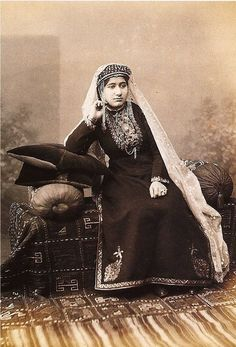 Armenian woman surrounded by textiles (late 19th century). From the costume of this woman one can conclude that she's most probably from Karin (Erzroum), Kars or Akhaltskha regions.