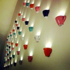 Lo confieso.  Veo material reciclado por todas partes.  Al ver esta pared llena de medias tazas con luz he pensado....
