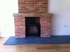 A Rais Q-Tee which looks really stylish in this red brick fire place.  We did all of the work here - fireplace and hearth.  The hearth is laid in our black, slate effect, non-scratch tiles.
