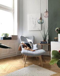 Gemütliche Ecke im Wohnzimmer - grauer Sessel, grüne Wand, grün und lilafarbene Lampen aus Glas und Pflanzen