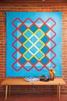 Sky blue quilt with warm accents on a brick wall :  Haven by Jenifer Dick   42quilts