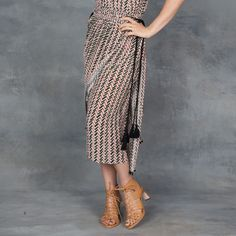 Mid length halter dress with plunging v-neckline and front layered panel with black rope side tassels.100% crinkled silk dress in multi color chevron print with pink, camel, and green. Fits true to size model is wearing size 2.