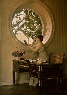 A lady by a large round window 1918.