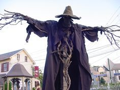 Twisted branches, old coat & hat, & a mask. Fantastic scarecrow.