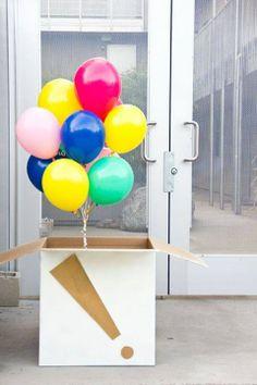 Una caja decorada con globos de latex con helio adentro para sorprender