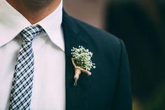 Boutonnière fleurs blanches sur costume bleu foncé
