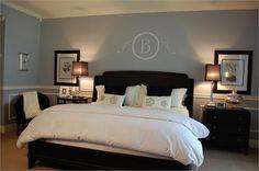 blue/purple walls, white linens, brown furniture