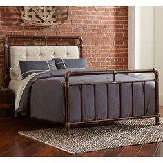 A Sturdy iron headboard and footboard softened with tufted fabric upholstery creates a beautiful upholstered iron bed. The iron bed is finished in Brown Copper with Antique Gold with the  Button Tufted Fabric Upholstered Headboard in Cream. Largo's Soho Iron Bed by Humble Abode.: