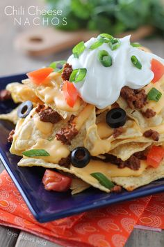 Chili Cheese Nachos are the perfect party food, with layers of beefy chili, homemade cheese sauce, and piled high with tasty toppings! Recipe at LoveGrowsWild.com