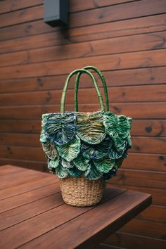 Straw basket bag is handmade in a structured tote silhouette with contrasting leaf detail and dual top handles Basket Bag, Human Trafficking, Day Bag, Gifts For Mom, Straw Bag, Artisan, Handmade, Bags, Florals