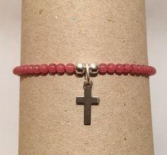Pulsera color rosa con cruz