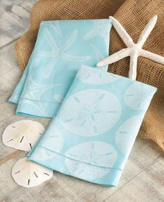 Starfish and Sand Dollar Hand Towels in a soothing sky blue with faded imprint.