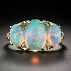 Antique Three-Stone Opal Ring. Enchanting times three! A luminous and shimmering trio of opals: a 2 carat in the center accompanied by a matched pair totaling 1.40 carats (3.40 carats total), glisten and glow with kaleidoscopic colors in this classic late-Victorian 'carved ring', masterfully hand crafted in rich 18K yellow gold - circa 1900. The opals are accented with four tiny old mine-cut diamonds set in between. #opal #rings #jewelry