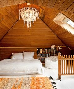 Attic: wood beadboard all around, fluffy white bed, and chandelier. [<3]