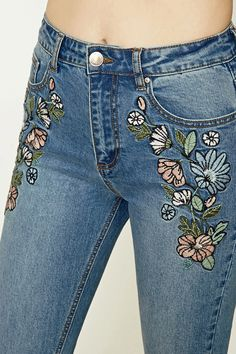 A pair of boyfriend jeans featuring floral embroidery on front, high-rise, a five-pocket construction, and a zip fly.