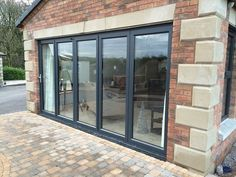 Aluminium framed doors The framing is dark grey RAL 7016 which contrasts against the brick work and sandstone facade.