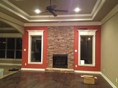 Orange - red accent wall with stone fireplace. Pan ceiling