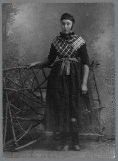 Vrouw in Staphorster streekdracht. Ze is gekleed in opknapdracht en is niet in de rouw. Op haar hoofd een ondermuts, zilveren oorijzer met spiraalvormige krullen aan de uiteinden en oorijzerband. Over de borstrok draagt ze een kraplap en een geruite schouderdoek, verder een schort met gedessineerd schortstukje en schoenen met zilveren gespjes. #Overijssel #Staphorst