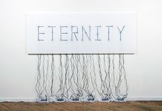 """""""'Eternity' is a wall mounted sculpture made by American artists Alicia Eggert & Mike Fleming, consisting of 30 electric clocks rear-mounted to a large sheet of white acrylic. During installation, the black hour and minute hands of the clocks are aligned to spell the word 'Eternity', and the clocks are plugged in to a series of power strips on the floor. The hands begin to move as soon as the switch on the last power strip is flipped..."""""""