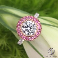 This round brilliant cut diamond is encompassed by a gorgeous halo of pink sapphires.